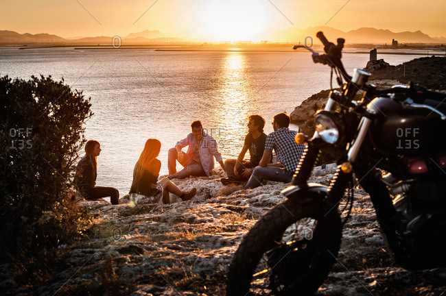 Five motorcycling friends taking a break on coast at sunset