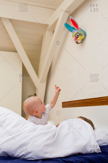 Baby girl pointing from bed whilst mother under covers
