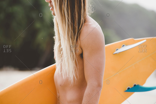 Midsection of a surfer with surfboard