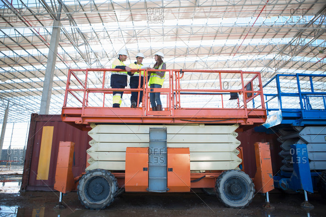 Low angle view of site managers and architect on viewing platform on construction site