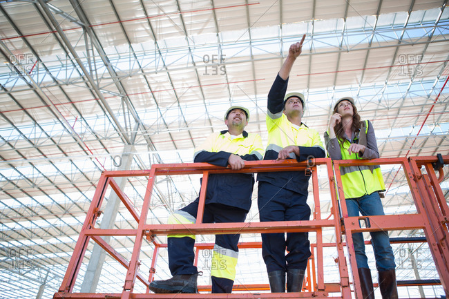 Low angle view of site managers and architect pointing from viewing platform on construction site