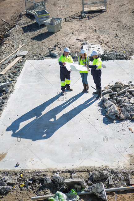 High angle view of architects and site manager meeting on construction site