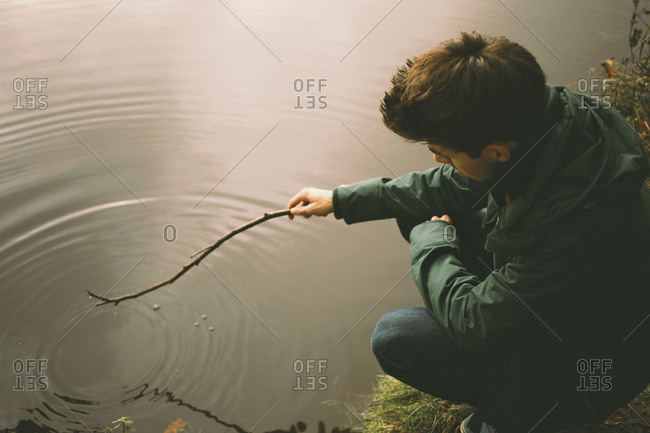Young man crouching on riverbank making ripples in water with twig