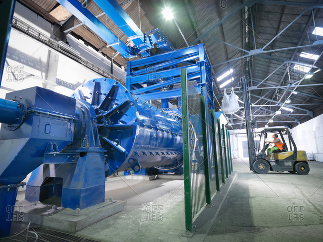 Worker in forklift truck loading metal ore in grinding mill
