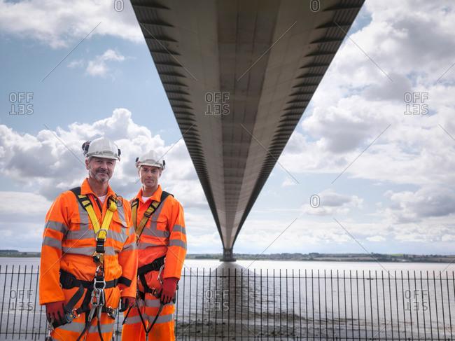 Portrait of bridge workers under suspension bridge