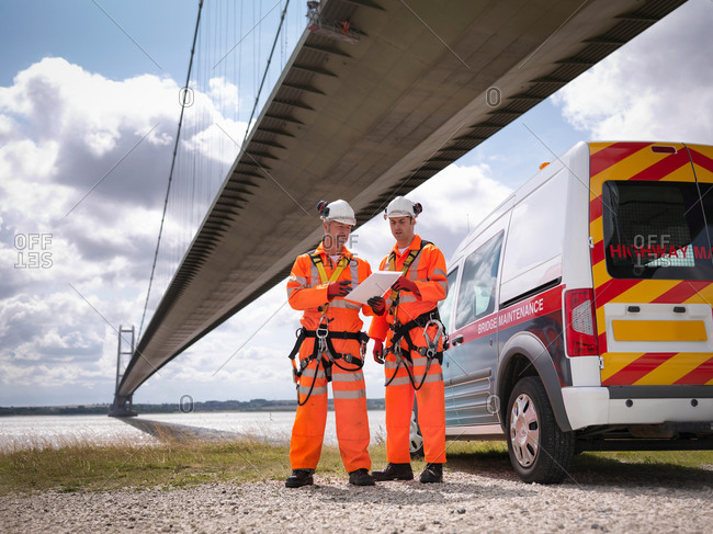 Bridge workers and support truck under suspension bridge