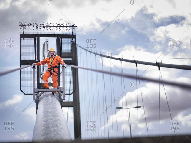Bridge worker walking down a cable of suspension bridge