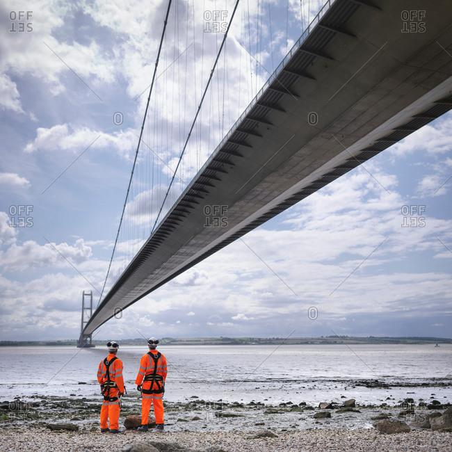 Bridge workers on beach under suspension bridge
