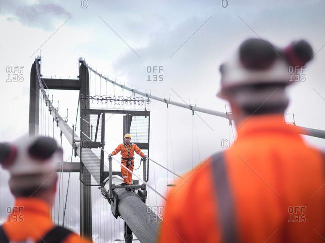 Bridge workers watching coworker on cable of suspension bridge