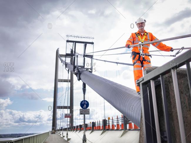 Bridge worker on cable of suspension bridge