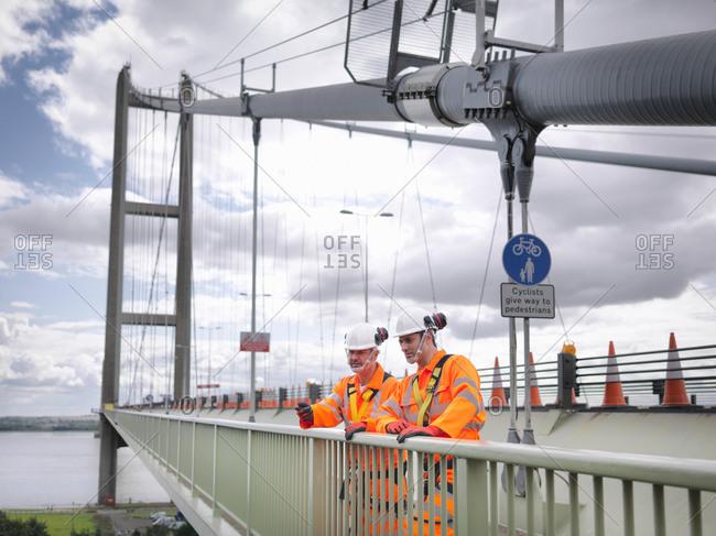 Two bridge workers on parapet of suspension bridge