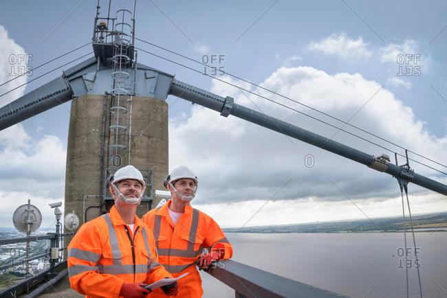 Two bridge workers on top of suspension bridge
