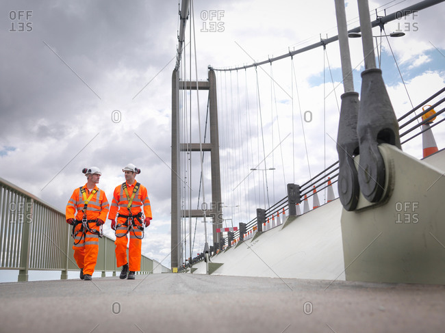 Bridge workers walking on parapet of suspension bridge