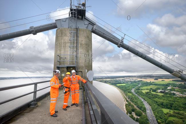 Three bridge workers on top of suspension bridge