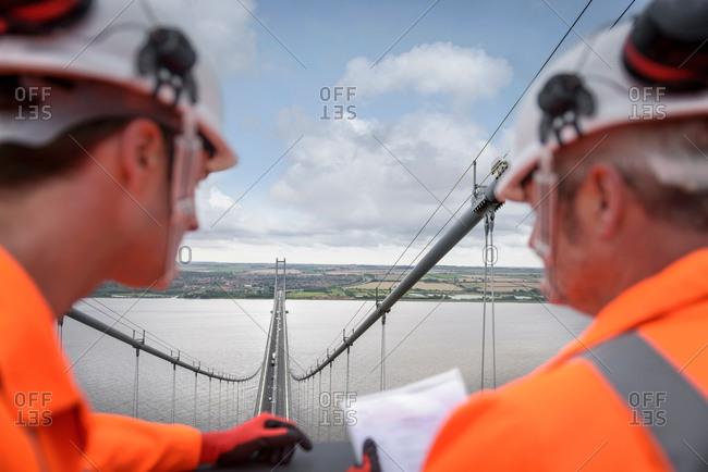 Bridge workers looking down from top of suspension bridge