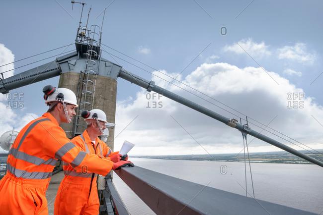 Profile of two bridge workers on top of suspension bridge