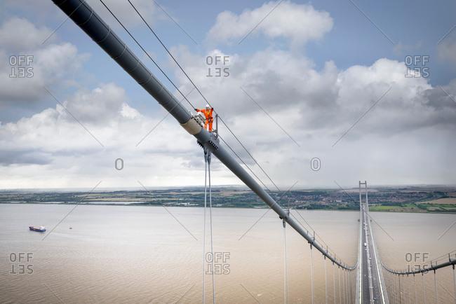 Bridge worker climbing on cable of suspension bridge