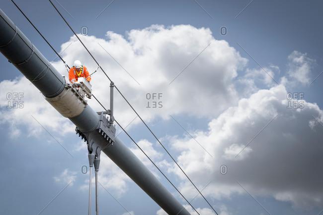 Bridge worker working on cable of suspension bridge