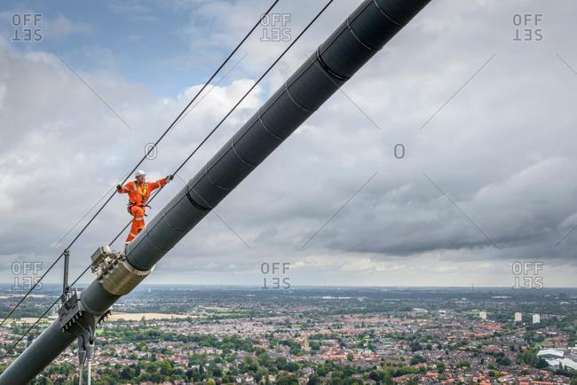 Bridge worker walking on cable of suspension bridge