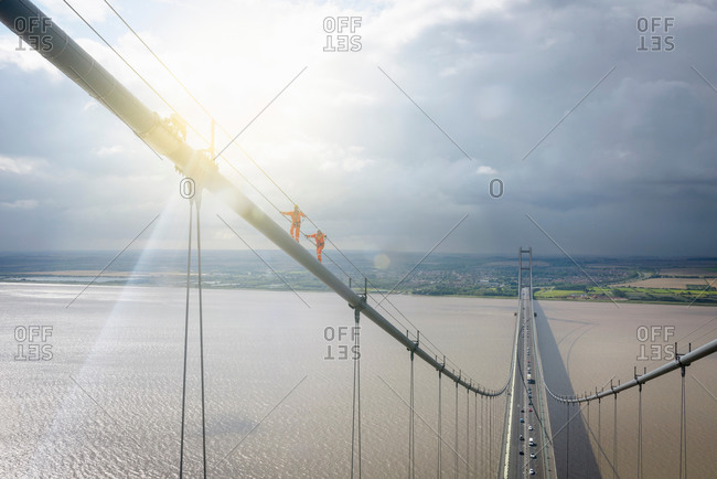 Two bridge workers walking on cable of suspension bridge under bright sunlight