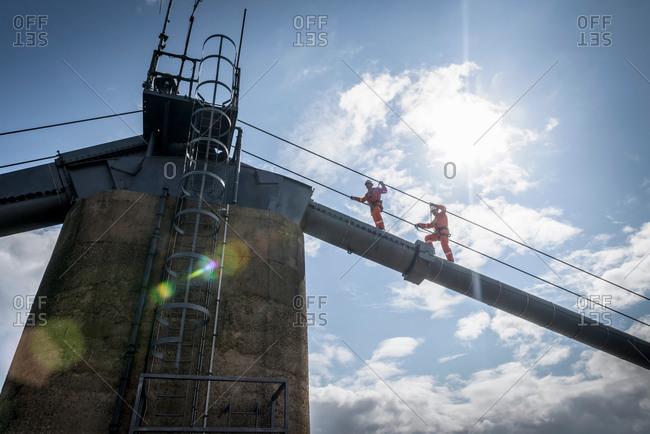 Bridge workers walking on cable of suspension bridge under bright sunlight