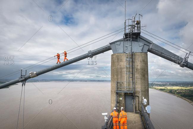 Bridge workers walking on cable of suspension bridge