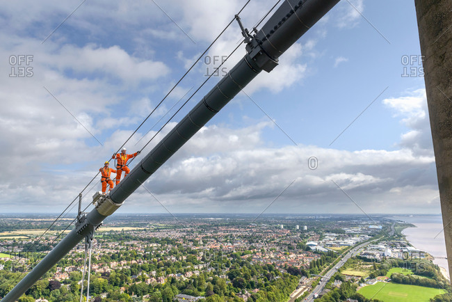 Bridge workers walking up cable of suspension bridge