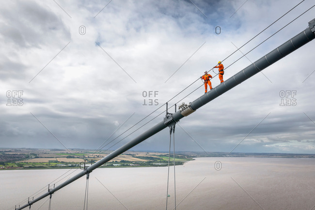 Two bridge workers working on cable of suspension bridge