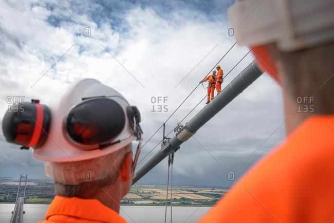 Bridge workers working on cable of suspension bridge