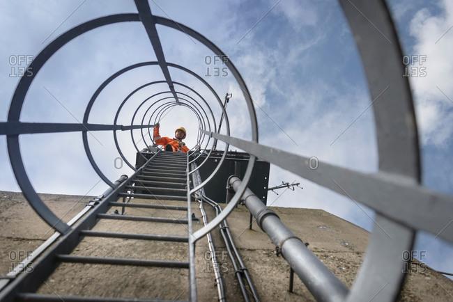 Bridge worker on ladder on top of suspension bridge
