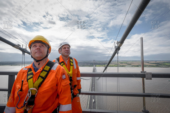 Portrait of bridge workers on top of suspension bridge