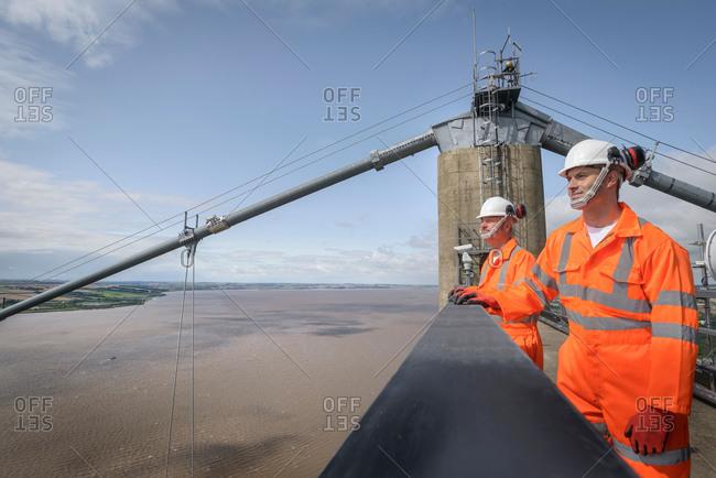 Bridge workers on top of suspension bridge