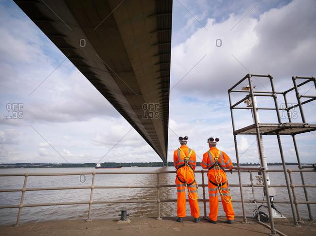 Bridge workers under suspension bridge