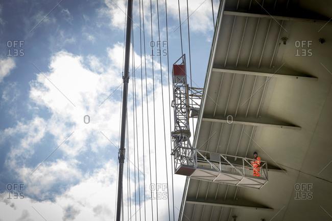 Bridge worker operating inspection gantry on suspension bridge