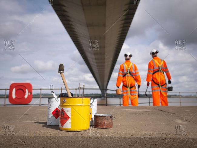 Bridge painters looking at  suspension bridge