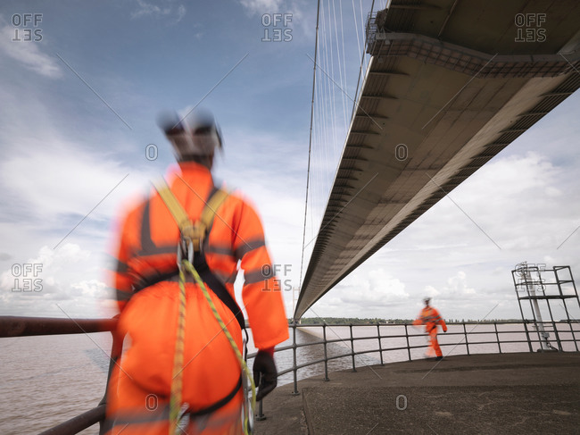 Bridge workers walking under suspension bridge