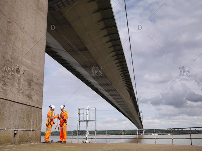 Bridge workers meeting under suspension bridge
