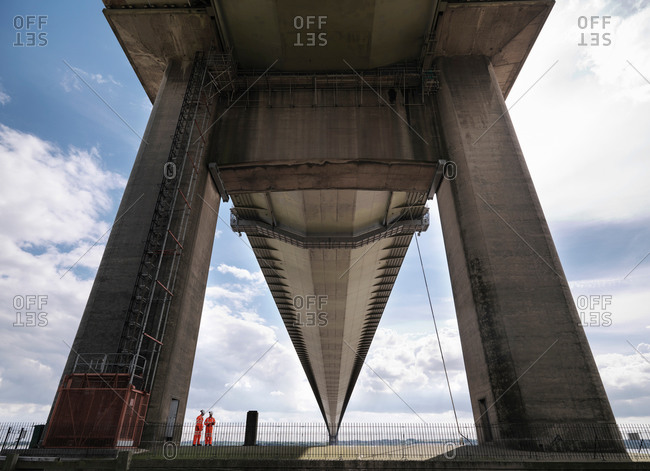 Bridge workers inspecting suspension bridge