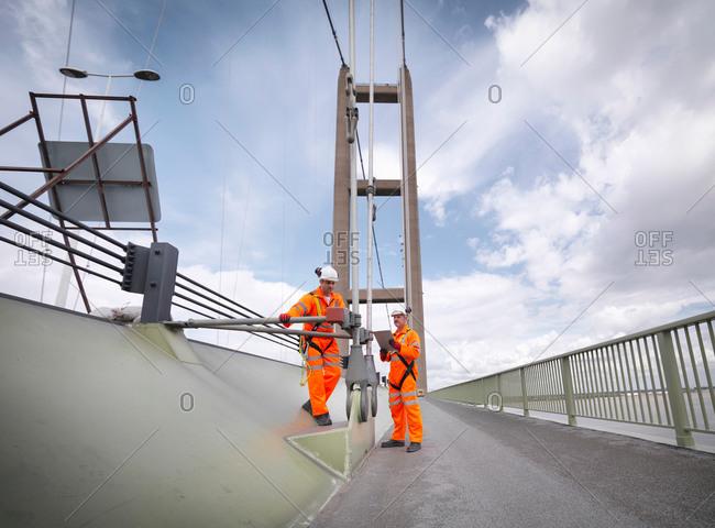 Bridge workers inspecting suspension bridge cables