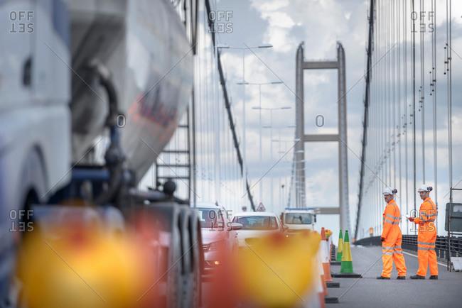 Bridge workers inspecting traffic on suspension bridge