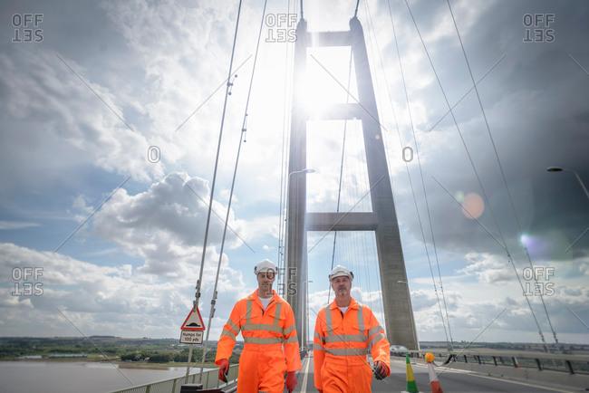 Workers walking along roadway of suspension bridge