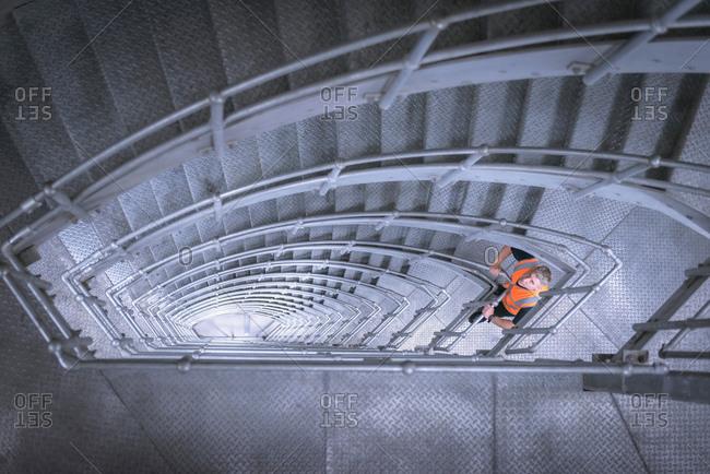 Worker in stairway of suspension bridge