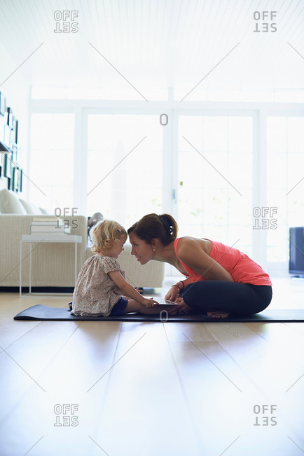 Mid adult mother and toddler daughter practicing lotus position in living room