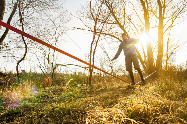Young man balancing on one leg on slackline in field landscape