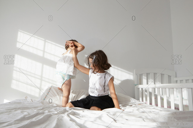 Girl giving helping hand to female toddler cousin to toddle on bed