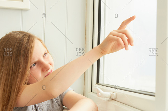 Girl pointing out of vacation apartment window
