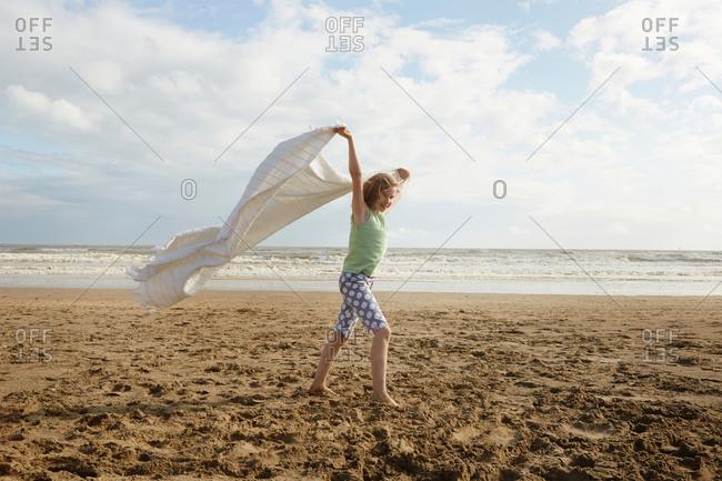 Girl holding up blanket on breezy beach, Camber Sands, Kent, UK