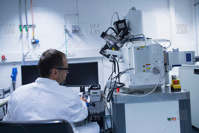 Lab assistant working with scanning electron microscope