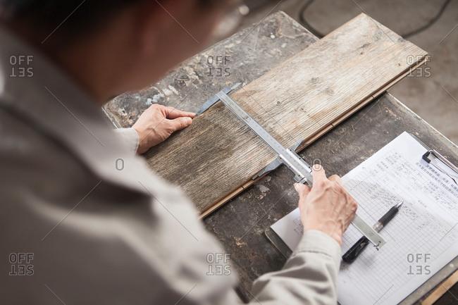 Carpenter measuring width of wood plank with vernier caliper in factory, Jiangsu, China