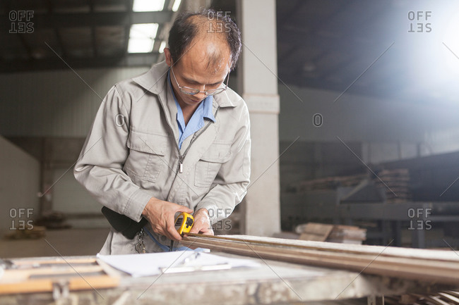 Carpenter using a tape measure to measure a wood plank with  in factory, Jiangsu, China